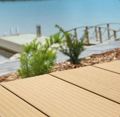 Puukomposiittilautaa merenrantaterassilla.